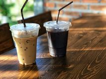 Choose what you are. differences in similarities. Ice black coffee and ice coffee cup on the wooden table with natural morning sunlight Stock Photos
