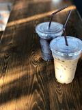 Choose what you are. differences in similarities. Ice black coffee and ice coffee cup on the wooden table with natural morning sunlight Royalty Free Stock Photography