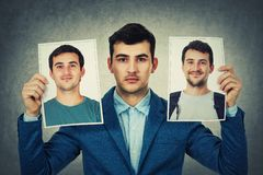 Choose your character. Young man holding two portrait photo sheets with different character. Change your personality, fake mask to hide the real expression of royalty free stock photo