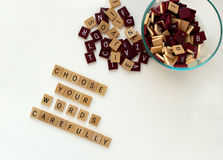 Choose Your Words Carefully. Glass bowl with lettered wooden tiles. Conceptual idea of choosing words carefully royalty free stock photos