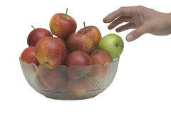 Choosing. Hand picking an apple from a glass bowl royalty free stock photography