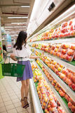 Choosing apples. Young beautiful woman choosing apples at the supermarket Royalty Free Stock Images