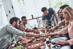 Choosing the best slice. Group of young people in casual wear eating and smiling while having a dinner party royalty free stock photo