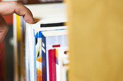 Choosing book. Photo of a man choosing a book with his finger royalty free stock image