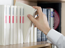 Choosing book Hand of man in white sleeve cuff Royalty Free Stock Photos