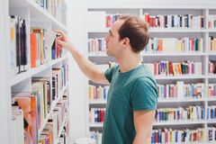 Choosing book in library or bookshop, student picking literature. Curious man choosing book in library or bookshop, student picking literature from the shelf Royalty Free Stock Image