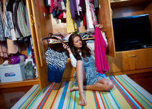 Choosing clothes. Teen girl choosing clothes in front of full closet Stock Image