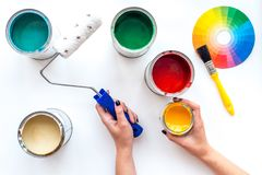 Choosing color for painting. Hands hold brush and paint roller on white background top view stock images