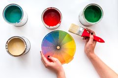 Choosing color for painting. Hands hold palette and brush on white background top view stock photos