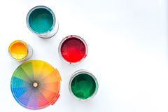 Choosing color for painting. Palette and paints in tin banks on white background top view copyspace royalty free stock photography