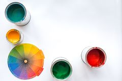 Choosing color for painting. Palette and paints in tin banks on white background top view copyspace royalty free stock photos