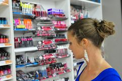 Choosing Cosmetics. Woman picking some cosmetics from the store Royalty Free Stock Photos