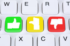 Choosing customer service quality feedback with thumbs up and do. Wn on computer keyboard Stock Photo