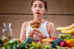 Choosing between dessert and healthy fresh food. Young woman feeling sorry for eating sweet croissant instead of healthy fruits and vegetables. Worry about Royalty Free Stock Photography