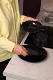 Choosing dinnner plates. Elderly woman in a kitchen holding a set of black ceramic plates Stock Photo