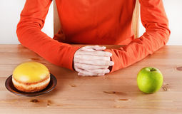 Choosing between doughnut and apple. Healthy living concept: choosing between doughnut symbolizing unhealthy food and green apple symbolizing healthy food stock photography
