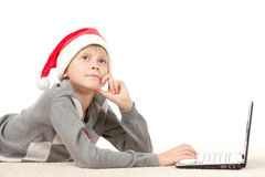 Choosing gifts for Xmas in internet. Pensive boy in Santa hat lying down on the floor choosing gifts for Xmas on laptop computer, looking upwards royalty free stock photography