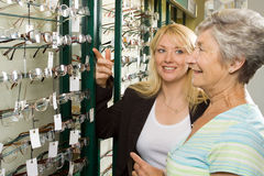 Choosing glasses at the optician. A lady choosing a pair of glasses in an optician Royalty Free Stock Image