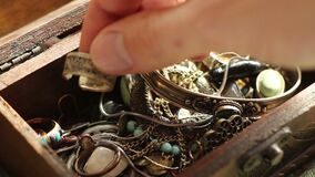 Choosing The Gold Ring. Close up of a hand searching in a glowing treasure chest and taking a gold ring stock video footage
