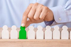 Choosing good leader worker from the crowd of bad. HR. Man in shirt takes good worker`s fingers stock photo