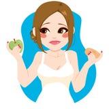 Choosing Healthy Apple. Sad young woman choosing healthy green apple instead of sweet doughnut Stock Image
