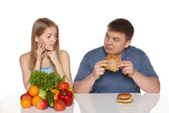 Choosing healthy eating concept. Woman looking whit dissaproval look as her boyfriend eating fast food, against white background Royalty Free Stock Photo