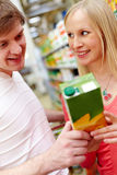 Choosing healthy food. Portrait of female looking at smiling man in supermarket while choosing juice Royalty Free Stock Image
