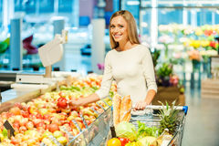 Choosing healthy food. Smiling young woman holding apple and looking at camera while standing in a food store Royalty Free Stock Image
