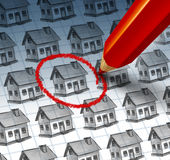 Choosing A home. And house search concept with a red pencil crayon highlighting a drawing from a group of houses as a symbol of finding the perfect family Royalty Free Stock Image