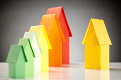 Choosing a House with an Energy Label. Selecting a yellow house from a row with colorful paper houses stock photo