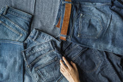 Choosing Jeans, Top View of Hand and Jeans stock photography