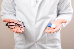 Choosing between lenses and glasses. Eye doctor choosing between eyeglasses and lenses standing in front of the eye chart in the cabinet Royalty Free Stock Photo