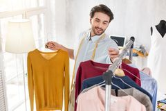 Inspired stylist working in his office. Choosing a look. Content bearded stylist smiling and looking at the sweaters in his collection Royalty Free Stock Photos