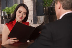 Choosing from the Menu. Beautiful middle-aged women reading Menu Stock Photography