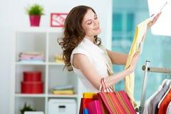 Choosing new dress. Portrait of pretty woman choosing new dress in clothing departmant Stock Photos