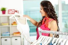 Choosing new dress. Portrait of pretty woman choosing new dress in clothing departmant Stock Photo