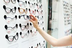 Choosing new optical glasses in optician shop. Woman`s hand choosing new optical glasses in optician shop Stock Photos