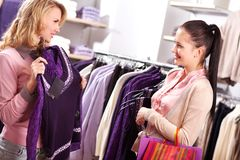 Choosing new sweater. Image of two pretty girls choosing clothes from new collection in department store Stock Image