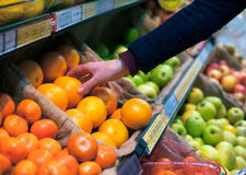 Choosing an orange in grocery store Royalty Free Stock Image