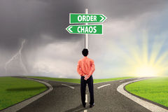Choosing order or chaos. Businessman standing on the road looking at signpost of order and chaos Stock Images
