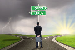 Choosing order or chaos 2. Businessman standing on the road looking at signpost of order and chaos Royalty Free Stock Images