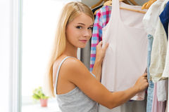 Choosing outfit for today. Smiling young woman choosing clothes and looking at camera while standing near her wardrobe Royalty Free Stock Images