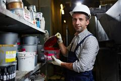 Choosing paint. Modern factory worker holding container with red paint in storehouse Stock Photos