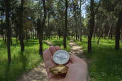 Choosing path. Compass being held out to determine direction Stock Photo