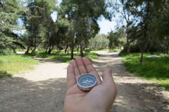 Choosing path. Compass being held out to determine direction Stock Photography