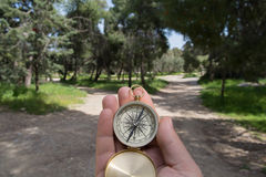 Choosing path. Compass being held out to determine direction Royalty Free Stock Photos