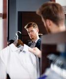 Choosing a perfect coat Stock Images
