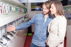 Choosing a phone. Shop assistant helping a customer choosing a smart phone Stock Image