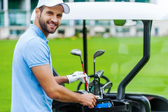 Choosing the proper driver. Handsome young male golfer choosing driver while standing near the golf cart Royalty Free Stock Photography