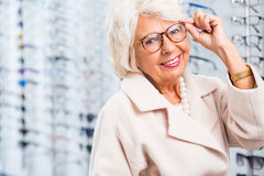 Choosing reading glasses. Elderly woman choosing reading glasses in optical shop Royalty Free Stock Photos